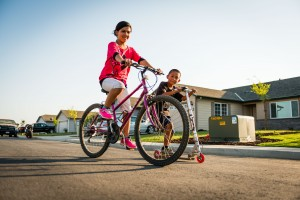 Self-Help Enterprises_Children riding bikes in community where parents built new and safe home 2014